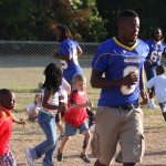 "Mulerider football players Caleb Patterson, from left, Darren ""Skinny"" Lewis, and Greg Nelson play freeze tag with a group of students at Westside Kindergarten."