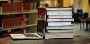 Photograph of a laptop along with a stack of books overlooking the Magale Library