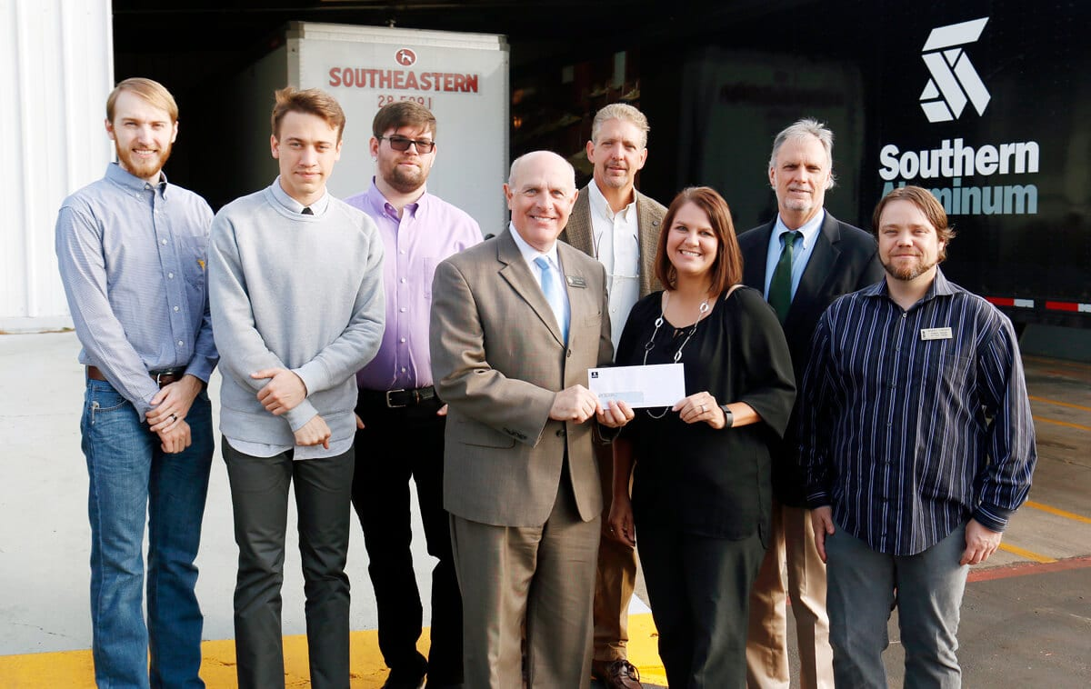 SAU President Dr. Trey Berry accepts a $5,000 check from Amanda Blanchard of Southern Aluminum. Pictured, from left, are SAU Art and Design students employed by Southern Aluminum Andrew Hinkle, Zach Miller, and Morgan Daniel, Berry, Chair of the Department of Art and Design Steven Ochs, Blanchard, Interim Provost and VPAA Dr. Ben Johnson, and Assistant Professor of Graphic Design Shawn Latham.